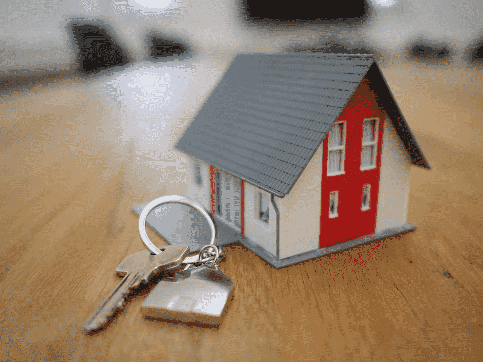 Estate planning concept with a miniature house and keys on the side.