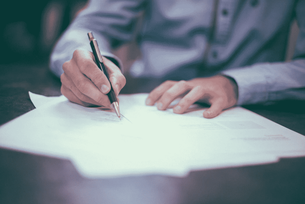 Man signing an insurance policy.